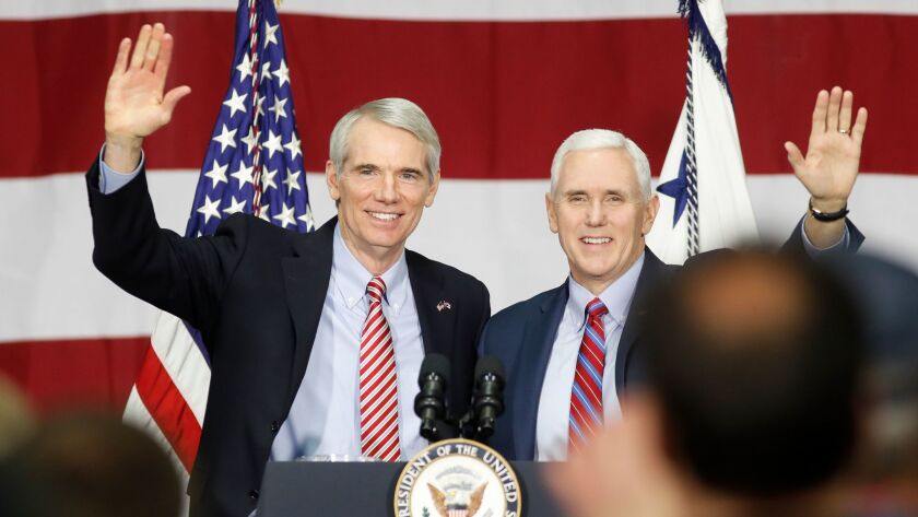 Sen. Rob Portman, R-Ohio, left, and Vice President Mike Pence wave to a group of spectators before g