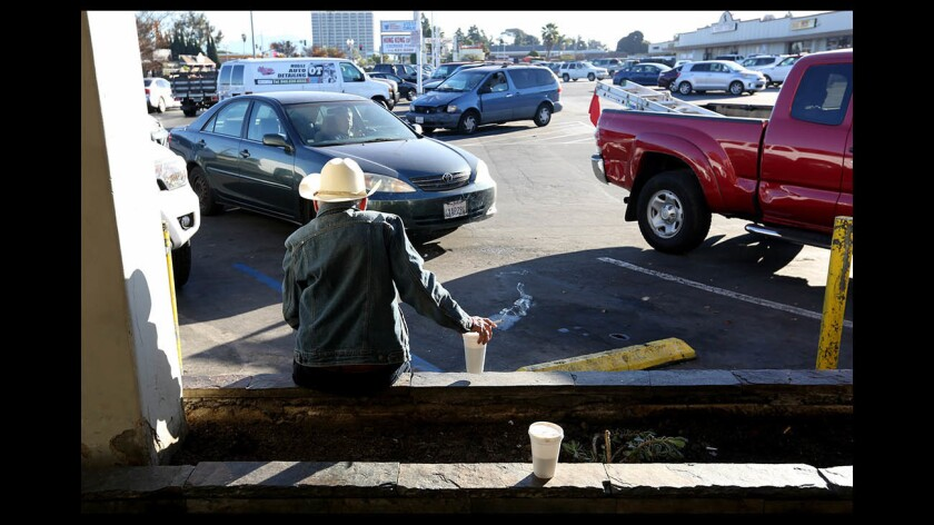 A 70-year-old man who lives in his vehicle has a cup of coffee in Costa Mesa.