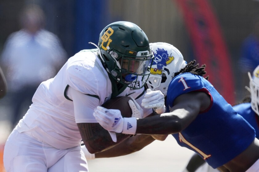 Baylor running back Trestan Ebner, left, is tackled by Kansas safety Kenny Logan Jr. (1) during the first half of an NCAA college football game in Lawrence, Kan., Saturday, Sept. 18 2021. (AP Photo/Orlin Wagner)