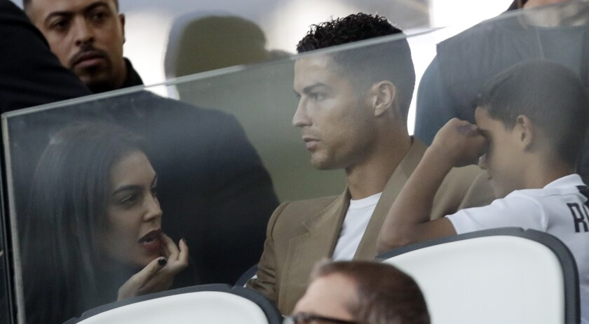 FILE - In this Oct. 2, 2018 file photo, Juventus forward Cristiano Ronaldo, center, is flanked by his girlfriend Georgina, left, and his son Cristiano Jr, as he sits in the stands during a Champions League, group H soccer match between Juventus and Young Boys, at the Allianz stadium in Turin, Italy. Ronaldo's legal fight with a woman who accuses the international soccer star of raping her in his suite at a Las Vegas resort more than 10 years ago is heading toward a court hearing before a federal judge in Las Vegas. (AP Photo/Luca Bruno, File)