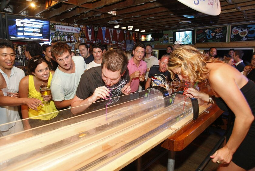 Patrons participate in a goldfish race at one of the many bars on Garnet Avenue.