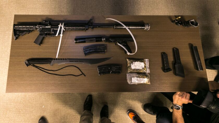 Los Angeles County Sheriff's Department deputies show a cache of illegal arms found in a suspect's duffel bag after arresting him Wednesday at a Pasadena Metro station.