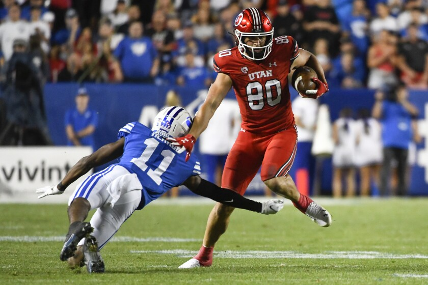 Utah tight end Brant Kuithe (80) jukes around Brigham Young defensive back Isaiah Herron (11) during the first half of an NCAA college football game Saturday, Sept. 11, 2021, in Provo, Utah. (AP Photo/Alex Goodlett)