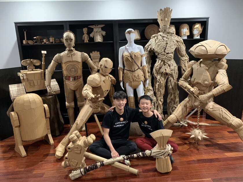 Connor (left) and Bauer Lee of the Cardboard Superheroes pose with some of their cardboard creations.