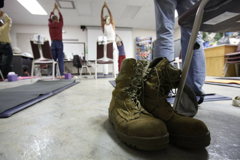 Silas Cochran placed his combat boots neatly next to his yoga mat. The Navy veteran says that in addition to helping his back, weekly yoga helps him slow down his thoughts.