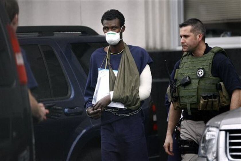 One of fourteen alleged Somali pirates is escorted out of the Federal Courthouse in Norfolk, Va., with U.S. Marshals on Thursday, March 10, 2011 after a federal grand jury indictment. (AP Photo/The Virginian-Pilot, Preston Gannaway)