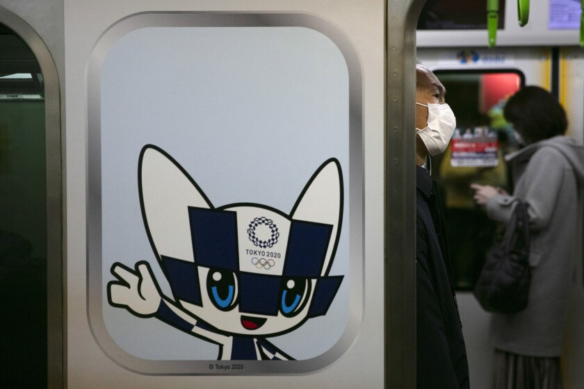 A man wearing a mask commutes in a train decorated with a poster showing Miraitowa, the official mascot of the Tokyo 2020 Olympics, Tuesday, March 3, 2020, in Tokyo. The Japanese government has indicated it sees the next couple of weeks as crucial to containing the spread of COVID-19, which began in China late last year. (AP Photo/Jae C. Hong)