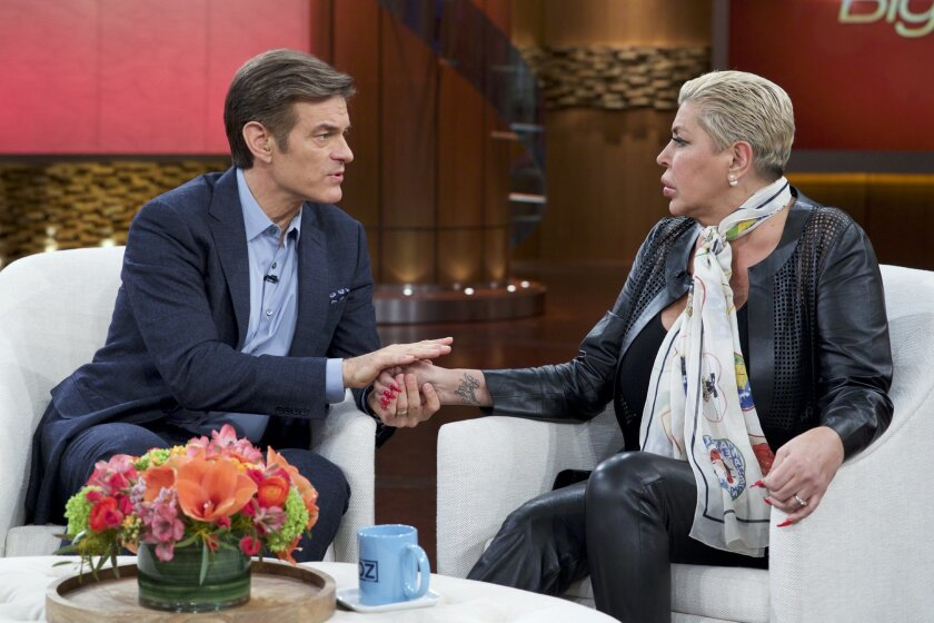 """In this image released by The Dr. Oz Show, Dr. Mehmet Oz, left, holds the hand of Angela """"Big Ang"""" Raiola during a taping of """"The Dr. Oz Show,"""" in New York. The reality TV star says she veers between hope and depression as she fights stage-four brain and lung cancer. In a tearful interview airing T"""