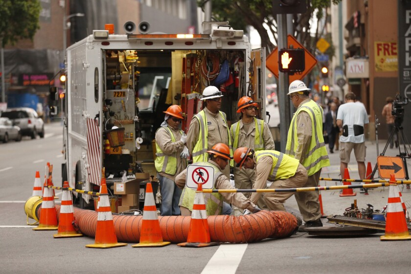 A DWP crew works near a downtown building at the corner of Wilshire and Flower in August.
