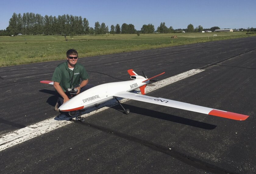 In this Aug. 4, 2015 photo provided by the University of North Dakota, UND drone pilot Whittaker Warrington poses next to a Draganflyer X4ES plane after a recent flight at the Lakota, N.D., airport for the Northern Plains UAS Test Site in northeastern North Dakota. The test site, one of six throughout the country, is the first to get approval from the FAA to fly drones above 200 feet and fly them at night. All the test flights are being flown by UND pilots. (Andrew Regenhard/University of North Dakota via AP)