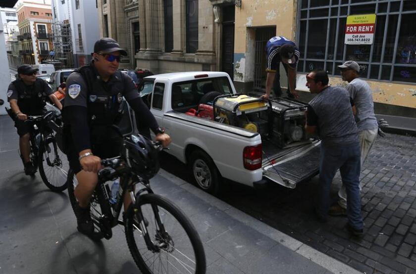 Dos agentes de policía pasan en bicicleta delante de unos ciudadanos cargando material en una camioneta en una calle de San Juan (Puerto Rico). EFE/ARCHIVO