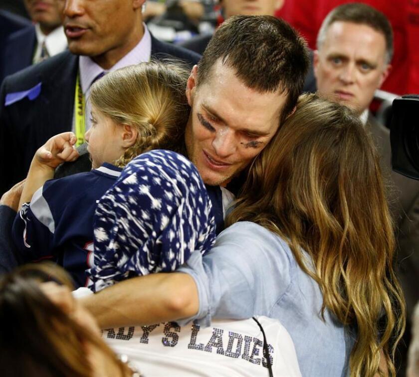 El mariscal de campo de los New England Patriots Tom Brady (c) abraza a su mujer Gisele Bundchen (d), y a su madre, tras ganar la Súper Bowl a los Falcons de Atlanta, antes de ayer. EFE