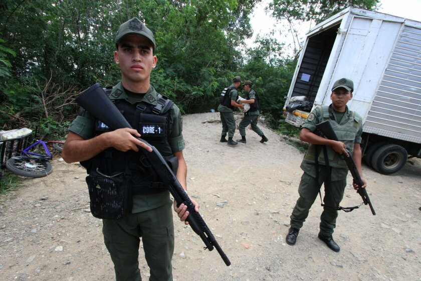 In this Monday, March 9,  2015 photo, Venezuelan Bolivarian National Guard officers handle seized merchandise that was being smuggled as others stand guard during a mission to stem the flow of contraband in San Antonio, Venezuela. President Nicolas Maduro almost daily blames the smuggling as a tool