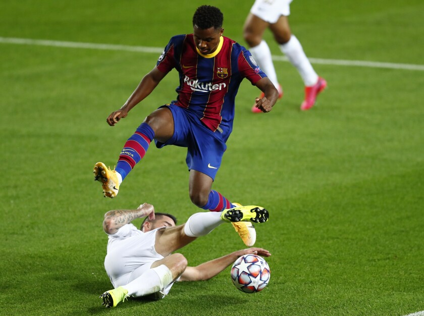 Ferencvaros' Endre Botka, bottom, tries to stop Barcelona's Ansu Fati during the Champions League group G soccer match between FC Barcelona and Ferencvaros at the Camp Nou stadium in Barcelona, Spain, Tuesday, Oct. 20, 2020. (AP Photo/Joan Monfort)