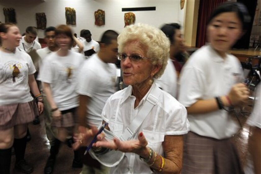 In this June 4, 2010 photo, English teacher Charlotte Drummond speaks to a student as other pass by at Cardinal Dougherty High School in Philadelphia. The archdiocese plans to close the Catholic school's doors this month after 54 years and more than 40,000 graduates. (AP Photo/Matt Rourke)