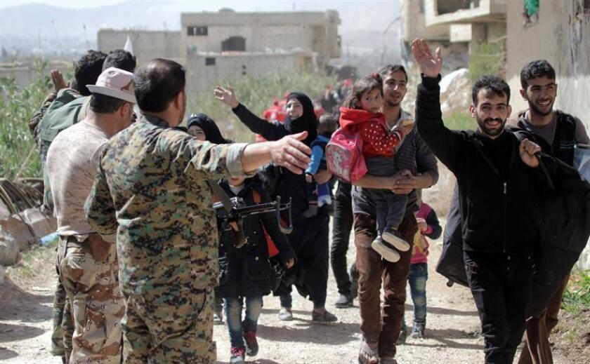 Cientos de civilies sirios salen de Guta Oriental, región que es el principal feudo opositor de las afueras de Damasco y objetivo de una ofensiva gubernamental, a través del corredor seguro de Al Wafideen, en Damasco, Siria, hoy, 21 de marzo de 2018. EFE/