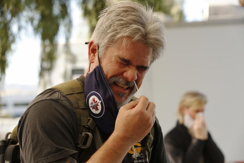 A man uses a nasal swab on himself for a coronavirus test