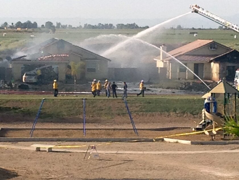 This photo provided by Isaac Ramos shows firefighters putting out a fire caused when a military jet crashed in residential neighborhood in Imperial, Calif., Wednesday, June 4, 2014. Witnesses say two houses caught fire after the crash. (AP Photo/Issac Ramos)