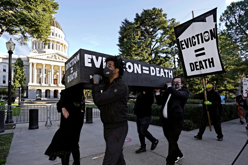 """Demonstrators carry a mock casket that says """"eviction = death"""" past the Capitol in Sacramento."""