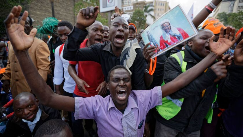 Supporters of opposition leader Raila Odinga, including one carrying a poster of Supreme Court Chief Justice David Maraga, demonstrate outside the Supreme Court in downtown Nairobi.
