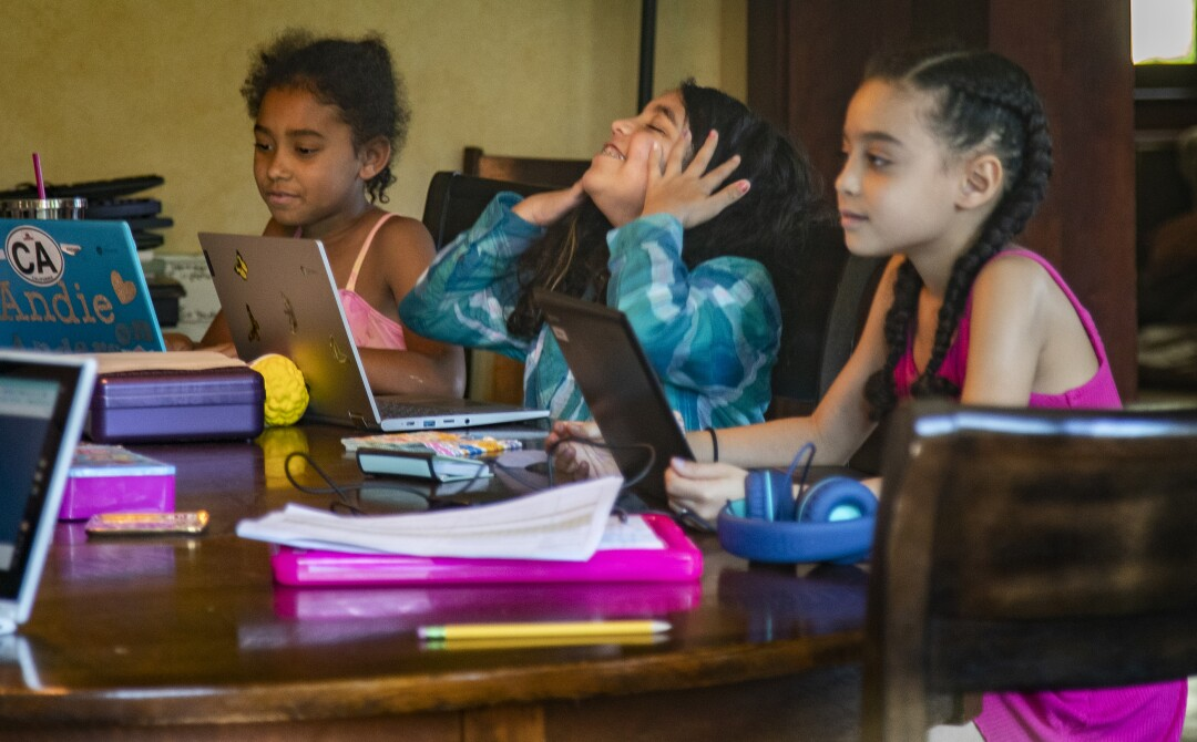Rosie Roth, en el centro, se toma un respiro de la clase de mecanografía sentada entre Andie Bristow, a la izquierda, y Allison Furbush en la mesa del comedor de los Bristows.