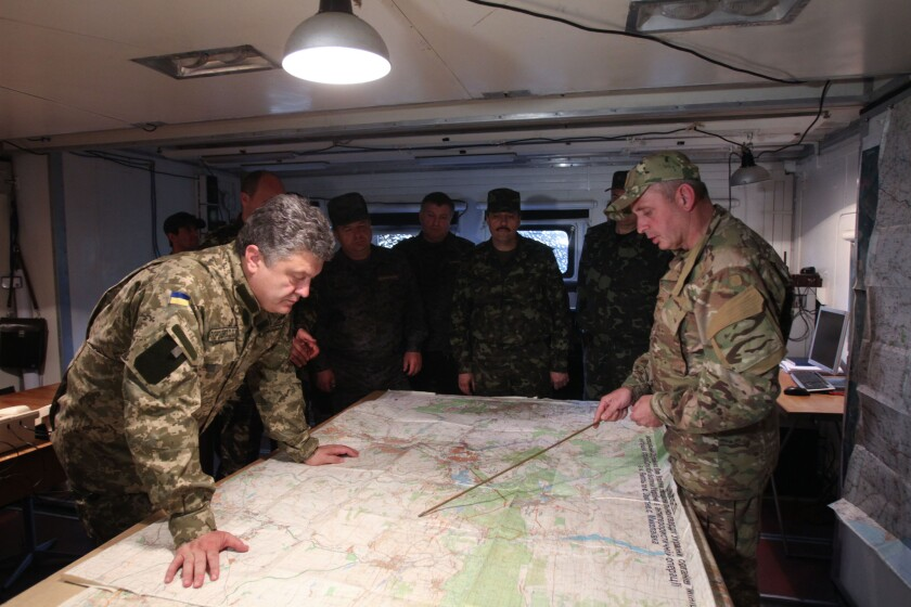 Ukrainian President Petro Poroshenko, left, examines a map at a military base close to Slovyansk, in eastern Ukraine.