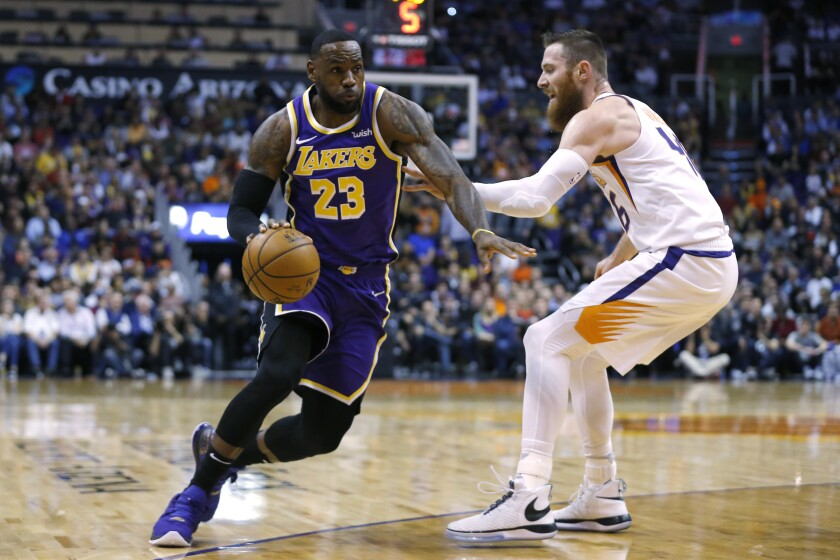 Lakers forward LeBron James drives on Phoenix Suns center Aron Baynes in the first half on Tuesday in Phoenix.