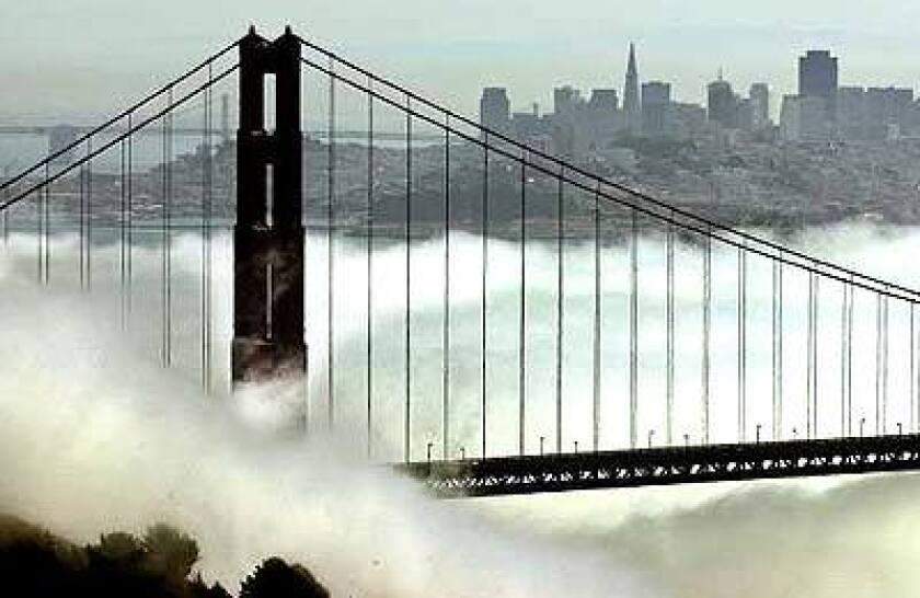The outline of the San Francisco skyline is seen beyond the fog-shrouded Golden Gate Bridge.