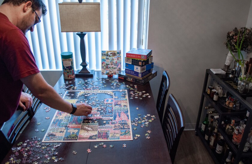 Jason Stump of La Mesa works on a puzzle to pass the time while sheltering at home.