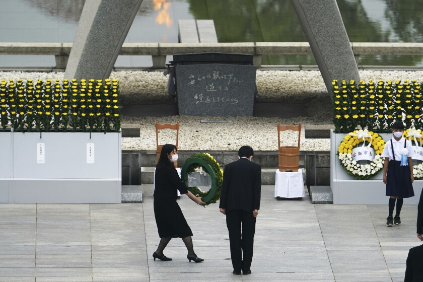 Japanese Prime Minister Shinzo Abe offers flowers to the Hiroshima Memorial cenotaph during Thursday's ceremony.