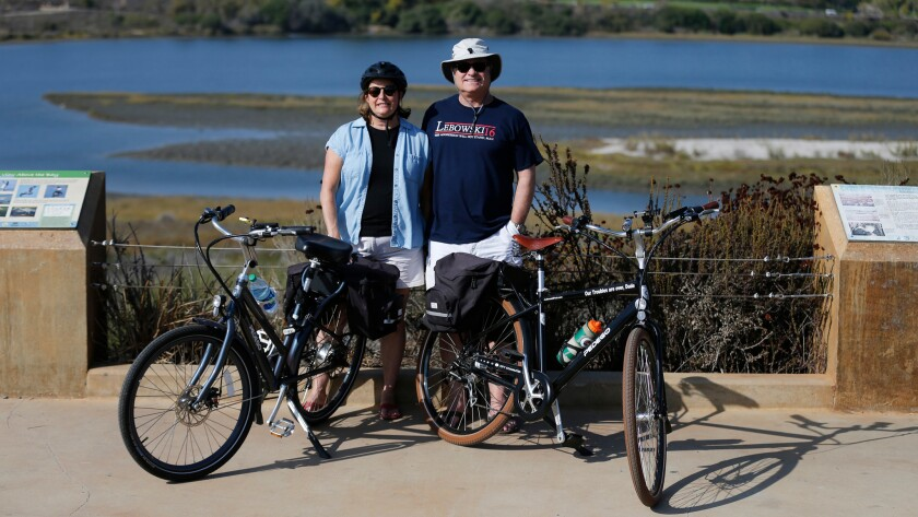 Dennis and Michelle Madden and their e-bikes at the Upper Newport Bay Nature Reserve trail in Newport Beach.