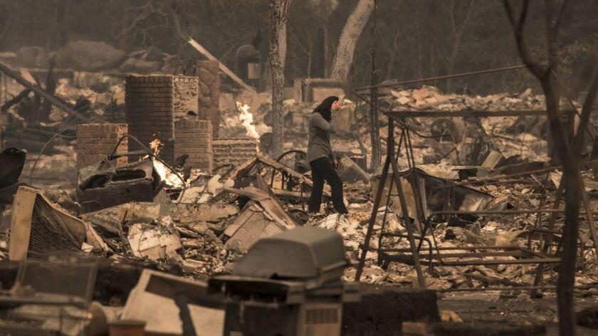 SANTA ROSA, CA -- MONDAY, OCTOBER 9, 2017: A Fountaingrove Village homeowner surveys her destroyed