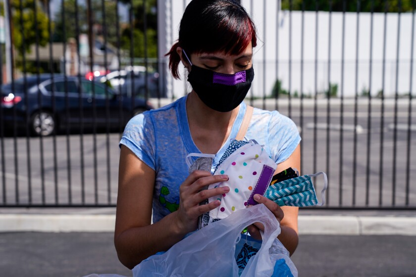 Eileen DenAdel of Culver City holds masks she made in the parking lot of the Costume Designers Guild on April 3 in Burbank.