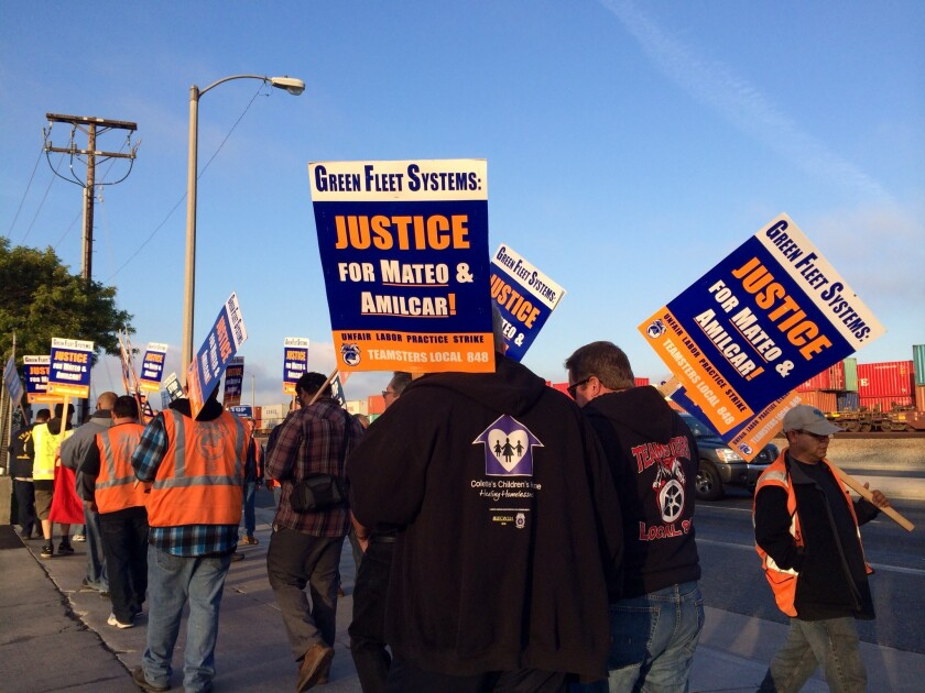 About two dozen truck drivers picket in front of Green Fleet Systems in Carson.