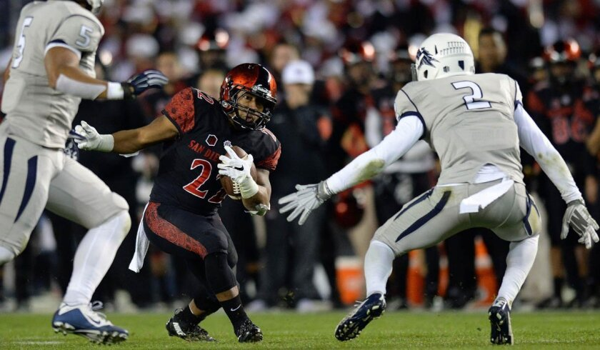 Nov 28, 2015; San Diego, CA, USA; San Diego State Aztecs running back Rashaad Penny (20) is defended by Nevada Wolf Pack defensive back Asauni Rufus (2) and linebacker Faigofie Faaituala (5) on a run during the first quarter at Qualcomm Stadium.