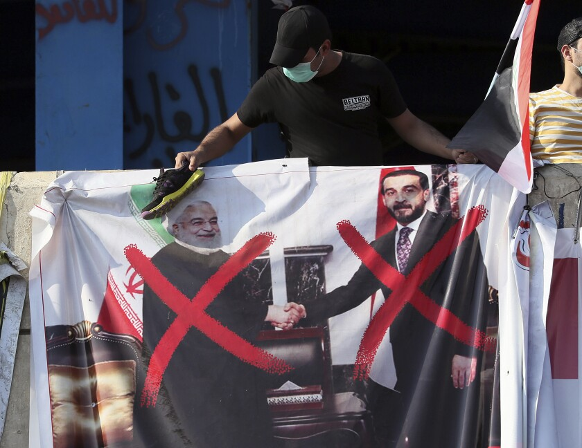 A defaced poster featuring Iranian President Hassan Rouhani, left, and Iraqi official Mohammed al-Halbousi is displayed during ongoing protests in Baghdad.