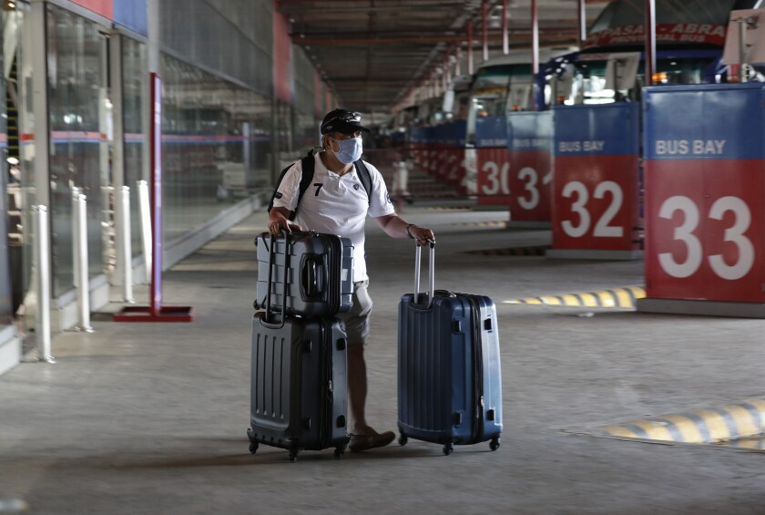 A Philippine seafarer pushes his bag at a bus terminal after spending weeks quarantined on a ship.