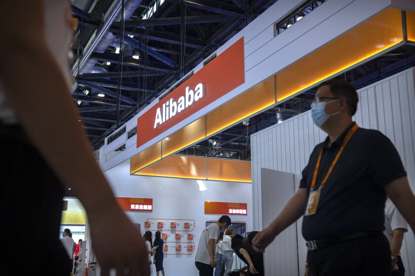 Visitors walk past a booth for Chinese technology firm Alibaba at the China International Fair for Trade in Services (CIFTIS) in Beijing, Friday, Sept. 3, 2021. E-commerce giant Alibaba Group said Friday it will spend $15.5 billion to support President Xi Jinping's campaign to spread China's prosperity more evenly, adding to pledges by tech companies that are under pressure to pay for the ruling Communist Party's political initiatives. (AP Photo/Mark Schiefelbein)