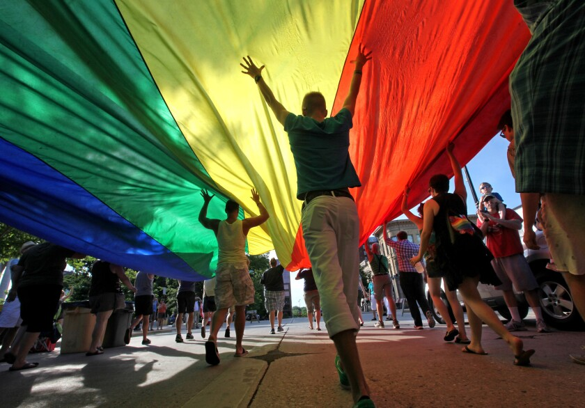 Supporters of a U.S. Supreme Court ruling which overturned the federal Defense of Marriage Act carry a large rainbow flag during a parade around the Wisconsin State Capitol in June, 2013.