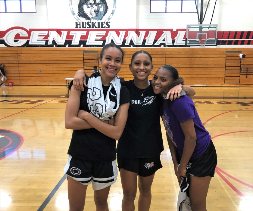 Corona Centennial girls' basketball team captains Trinity San Antonio, Jayda Curry, and Londynn Jones gather for a photo.
