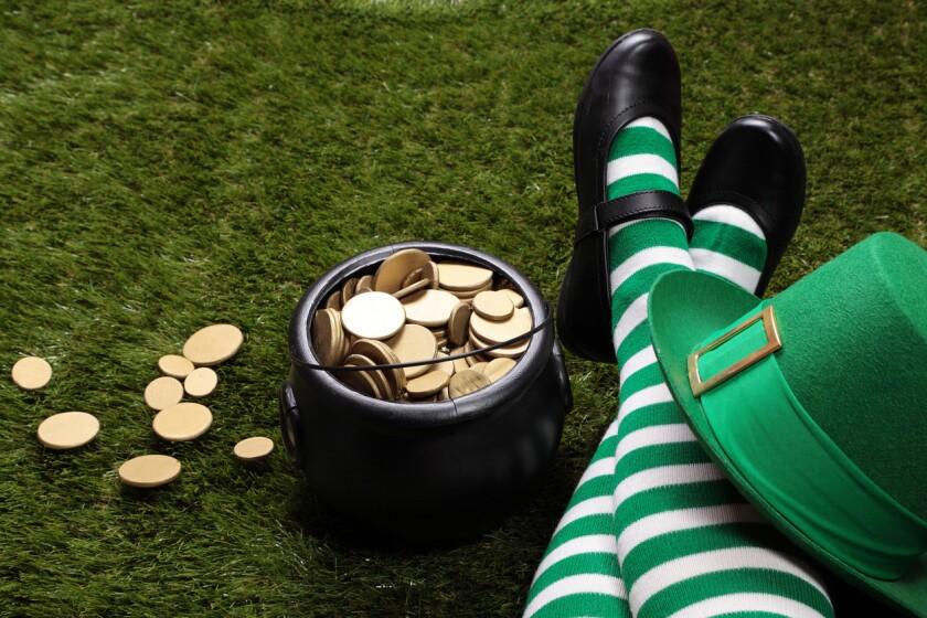 Female Leprechaun on the grass next to a pot of gold.