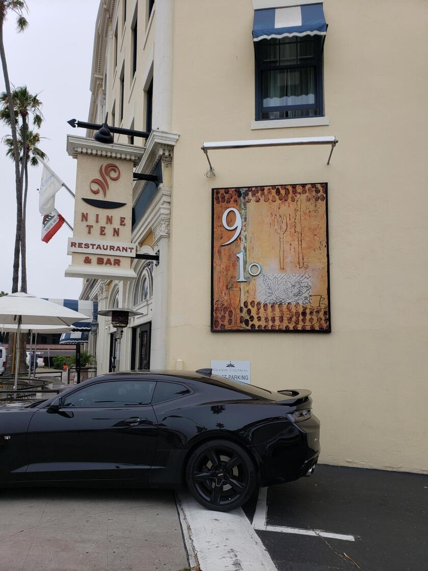 The NINE-TEN Restaurant within the Grande Colonial Hotel features a small mural including the number 910 on the side of the building at 910 Prospect St., La Jolla.