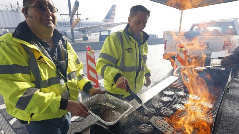 Airport operation workers wearing fluorescent safety jackets flipped burgers and hot dogs on a grill