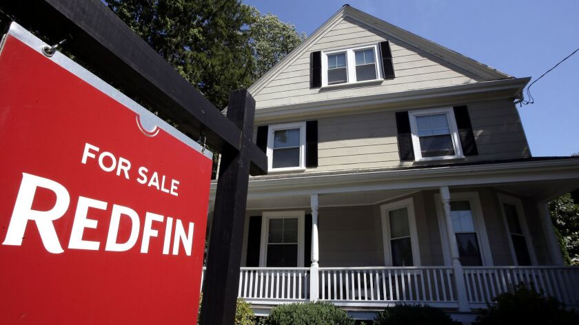 FILE - In this July 9, 2018, file photo, a for sale sign stands outside a pre-existing home, in Walp