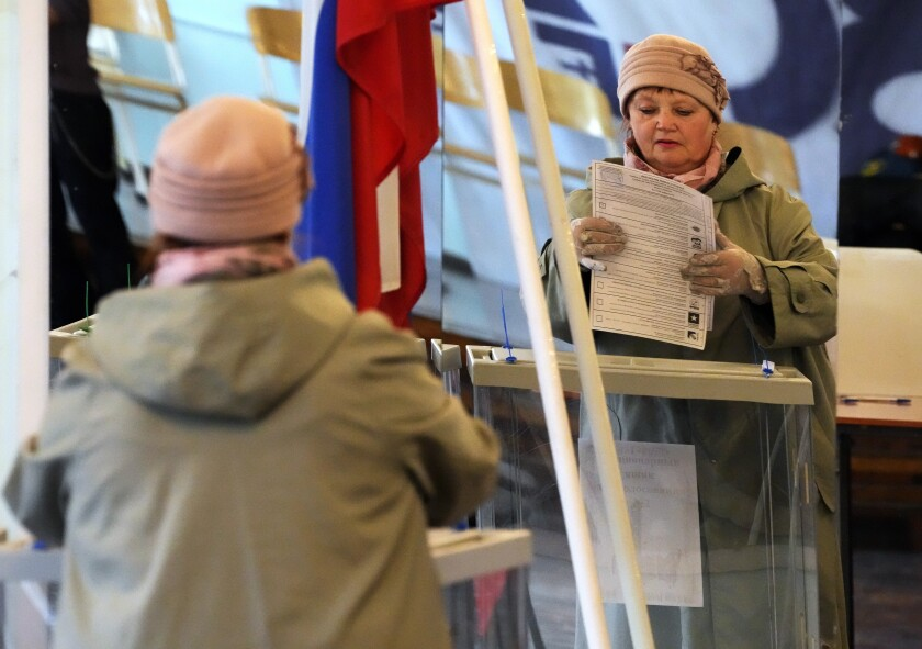 A woman reflected in a mirror casts her ballot during the State Duma, the Lower House of the Russian Parliament and local parliament elections at a polling station in St. Petersburg, Russia, Sunday, Sept. 19, 2021. Sunday will be the last of three days voting for a new parliament, but there seems to be no expectation that United Russia, the party devoted to President Vladimir Putin, will lose its dominance in the State Duma. (AP Photo/Dmitri Lovetsky)