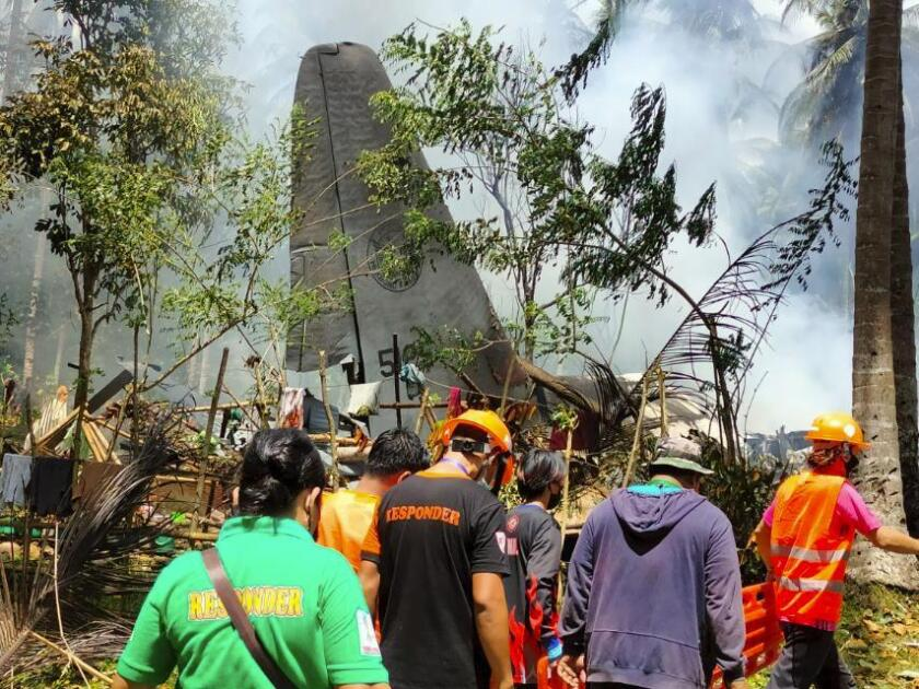 In this photo released by the Joint Task Force - Sulu, rescuers search for bodies from the site where a Philippine military C-130 plane crashed in Patikul town, Jolo province, southern Philippines on Sunday, July 4, 2021. The Philippine air force C-130 aircraft carrying troops crashed in a southern province after missing the runway Sunday, killing more than a dozen military personnel while at least 40 were rescued from the burning wreckage, officials said. (Joint Task Force-Sulu via AP)