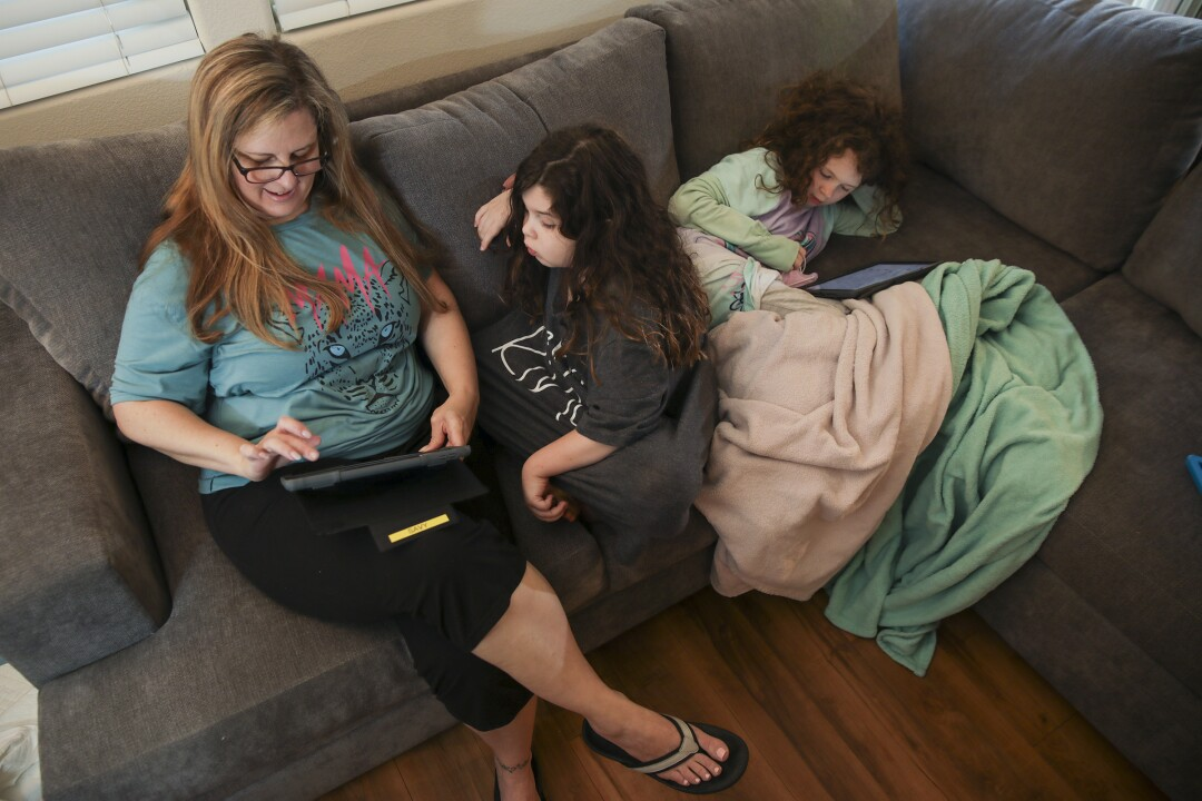 Alison Goldberg, left, with her 7-year-old twins Madelynn Singer, center, and Savannah Singer at home.