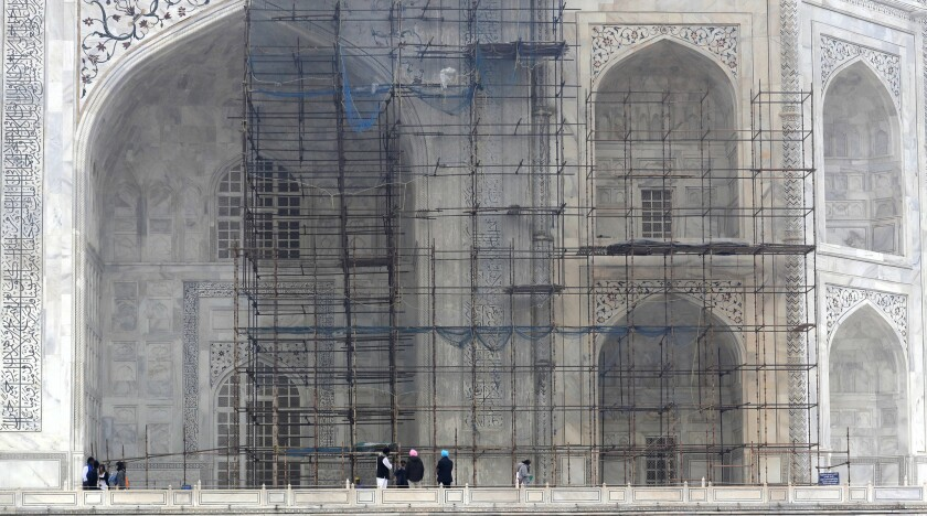 FILE - In this Dec. 5, 2017 file photo, tourists walk past a discolored wall of the Taj Mahal caused