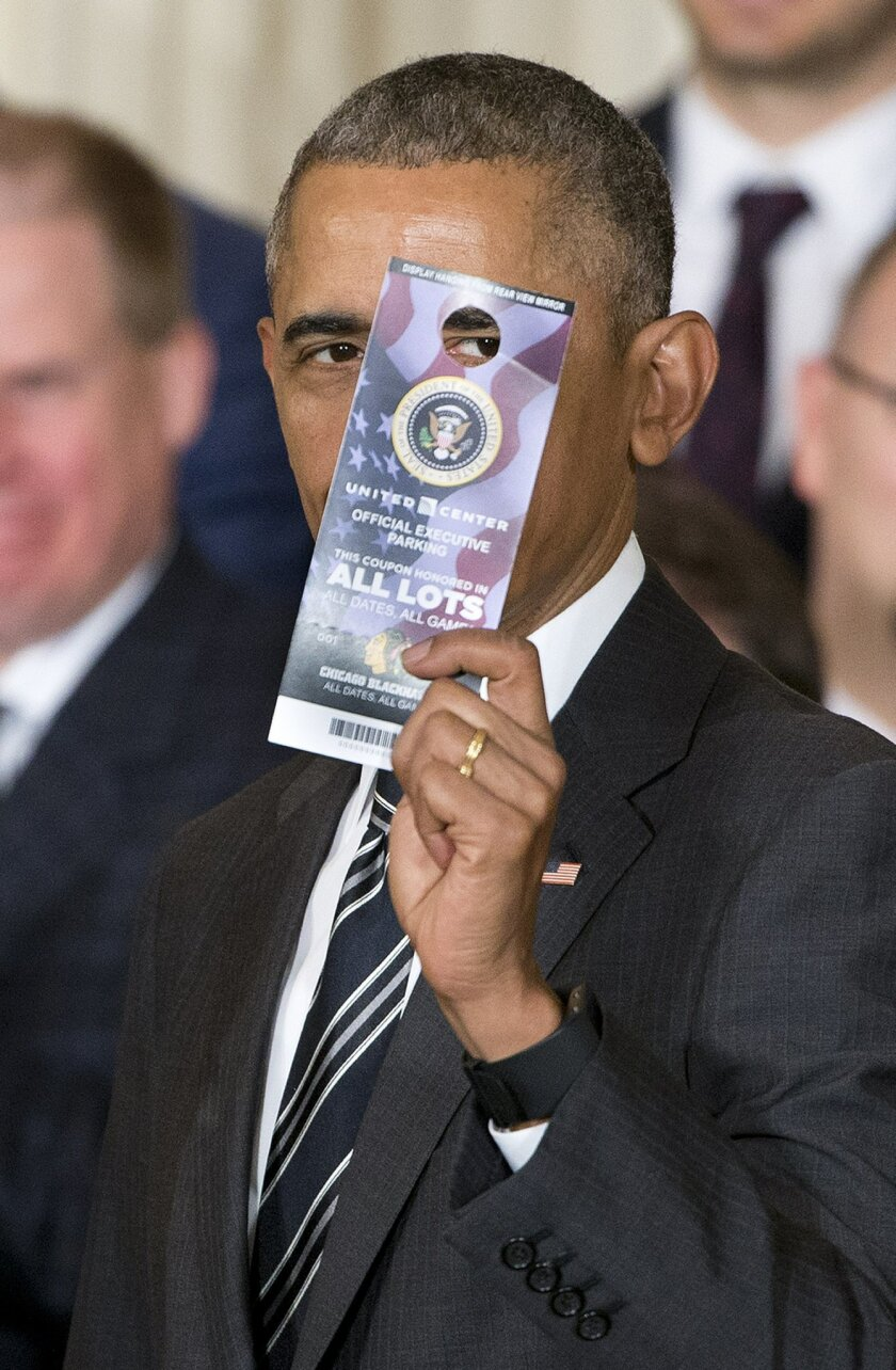President Barack Obama holds up a parking pass that was presented to him by Rocky Wirtz,  Chairman of the team, during a ceremony to honor the 2015 NHL Stanley Cup Champion Chicago Blackhawks in the East Room of the White House in Washington, Thursday, Feb. 18, 2016. The parking pass is good for al