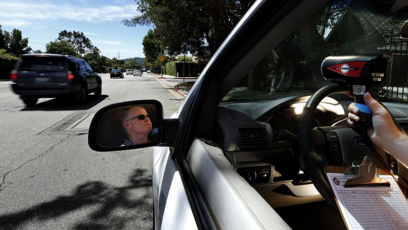 A Los Angeles Department of Transportation employee uses a laser gun to measure driver speeds in the San Fernando Valley.